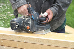 The man  processes a board a electric planer outdoors. The man with the injured finger processes a board a electric planer outdoors Royalty Free Stock Photos