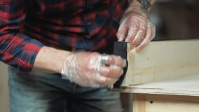 Man processes the wood protective fluid. Man wearing protective gloves handles wood protective liquid stain stock footage