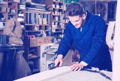 Man processing plank at workshop Stock Images