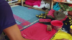 Man produces stamp print cloth at the workshop at the New Market in Dhaka, Bangladesh. stock video footage