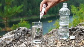 Man produces temperature measurement in Celsius in glass of water, on mountainous area. Health and ecology slowmotion. Man produces temperature measurement of stock video footage