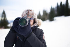 Man with professional camera photographing the mountain.Taking a photo of a mountain landscape. Hiker with photo camera and telephoto lens standing on top of Stock Photos