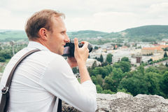 Man with professional photo camera take landscape picture Stock Photo