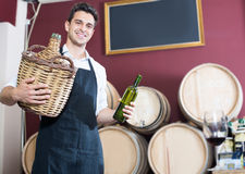 Man professional seller in apron holding bottle with wine. Glad man professional seller in apron holding big wicker bottle with wine in store Royalty Free Stock Images