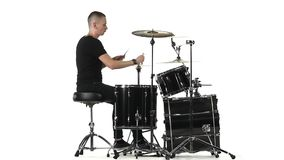 Man professionally plays percussion instruments . White background. Side view. Slow motion. Man sitting on a chair beautifully and professionally vigorously stock video