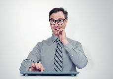 Man programmer in glasses with keyboard in front of computer Royalty Free Stock Photos