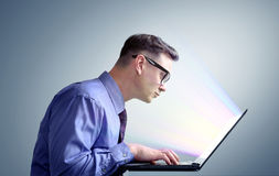 Man programmer in shirt and glasses sitting at a laptop Royalty Free Stock Image