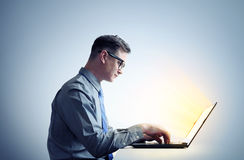 Man programmer in shirt and glasses sitting at a laptop Stock Photos
