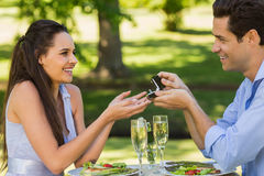 Man propose woman while they have romantic date at an outdoor café Stock Photography