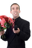 Man Proposing. A young man wearing a suit and holding a ring box and a bouquet of flowers, isolated against a white background Royalty Free Stock Photo