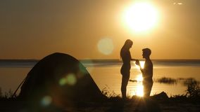 Man proposing beloved woman on the beach at sunset. Silhouettes of kneeled man proposing his beloved woman on the beach at sunset. Boyfriend putting engagement stock video