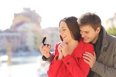 Man proposing marriage to his happy girlfriend. In a coast town during winter holiday royalty free stock images