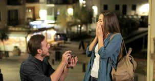 Man proposing marriage to his happy girlfriend. In a town in the night stock footage