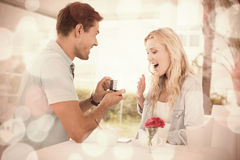 Man proposing marriage to his shocked blonde girlfriend. On the cafe terrace on sunny day Royalty Free Stock Photography
