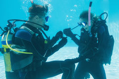 Man proposing marriage to his shocked girlfriend underwater in scuba gear Stock Images