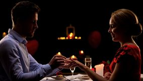 Man proposing to beloved lady, putting precious ring on finger, romantic dinner stock photo