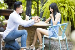 Man proposing to girlfriend offering engagement ring Stock Photos