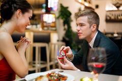 Man proposing to his girlfriend. While they are having a romantic date at the restaurant Royalty Free Stock Photos