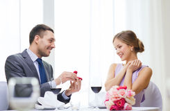Man proposing to his girlfriend at restaurant. Restaurant, couple and holiday concept - smiling men proposing to his girlfriend at restaurant Royalty Free Stock Image