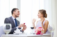 Man proposing to his girlfriend at restaurant. Restaurant, couple and holiday concept - smiling men proposing to his girlfriend at restaurant Stock Photography