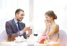 Man proposing to his girlfriend at restaurant. Restaurant, couple and holiday concept - smiling men proposing to his girlfriend at restaurant Stock Photo