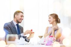 Man proposing to his girlfriend at restaurant. Restaurant, couple and holiday concept - smiling men proposing to his girlfriend at restaurant Stock Image