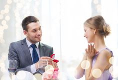 Man proposing to his girlfriend at restaurant. Restaurant, couple and holiday concept - smiling men proposing to his girlfriend at restaurant Royalty Free Stock Photos
