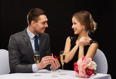 Man proposing to his girlfriend at restaurant. Restaurant, couple and holiday concept - smiling men proposing to his girlfriend at restaurant Royalty Free Stock Photography