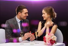 Man proposing to his girlfriend at restaurant. Restaurant, couple and holiday concept - smiling men proposing to his girlfriend at restaurant Stock Images