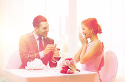 Man proposing to his girlfriend at restaurant. Restaurant, couple and holiday concept - smiling men proposing to his girlfriend at restaurant Stock Photos