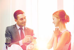 Man proposing to his girlfriend at restaurant. Restaurant, couple and holiday concept - smiling men proposing to his girlfriend at restaurant Royalty Free Stock Images