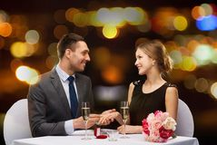 Man proposing to his girlfriend at restaurant Stock Photo