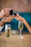Man proposing to woman offering engagement ring. In restaurant Royalty Free Stock Photography