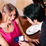 Man proposing to woman in restaurant Royalty Free Stock Photography