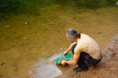 Man, prospector panning gold in a river with sluice box Stock Photos