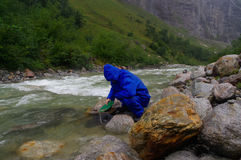 Man prospector panning gold on a river with sluice box  rainy da Stock Photo