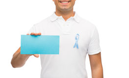 Man with prostate cancer awareness ribbon and card. Medicine, health care, gesture and people concept - close up of middle aged man in t-shirt with sky blue royalty free stock images
