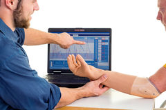 Man with prosthetic arm seeks help from technician. Computer-based adjusting. Stock Photos