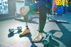 Man with prosthetic leg in modern gym. Close-up of unrecognizable man with prosthetic leg sitting in modern gym and resting between exercises with dumbbells royalty free stock photo