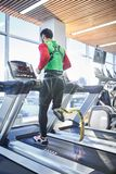 Man with prosthetic leg running on treadmill. Rear view of young disabled man with fitness prosthetic leg running on treadmill while training alone in modern royalty free stock photo