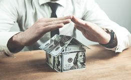 Man protect house of dollars. House insurance Stock Photography
