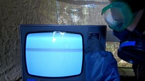 Man in protect suit turns on old TV. Concept post apocalypse