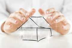 Man protecting a house with his hands Royalty Free Stock Images