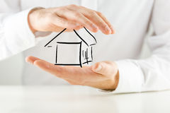 Man protecting a house with his hands Stock Photos