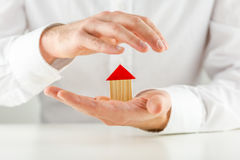 Man protecting a model house in his hands Royalty Free Stock Photo