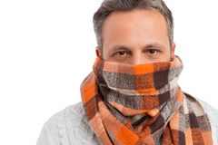 Man protecting nose and mouth with scarf. Man protecting nose and mouth with orange scarf covering face as cold weather fashion concept isolated on white studio royalty free stock image
