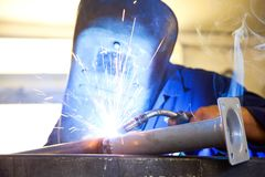 Man with protection is welding iron. Handcraft in workshop, hard work Stock Photo
