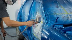 Spray gun with paint for painting a car royalty free stock images