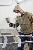 Man in protective clothes and respirator paints car details. In paint-spraying booth stock images
