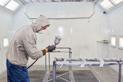 Man in protective clothes works in paint-spraying booth. Man in protective clothes and respirator works in paint-spraying booth stock photography